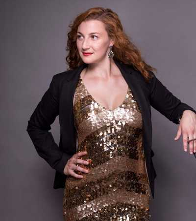 Alaina Viau posing in a gold dress with her hand on her hip.